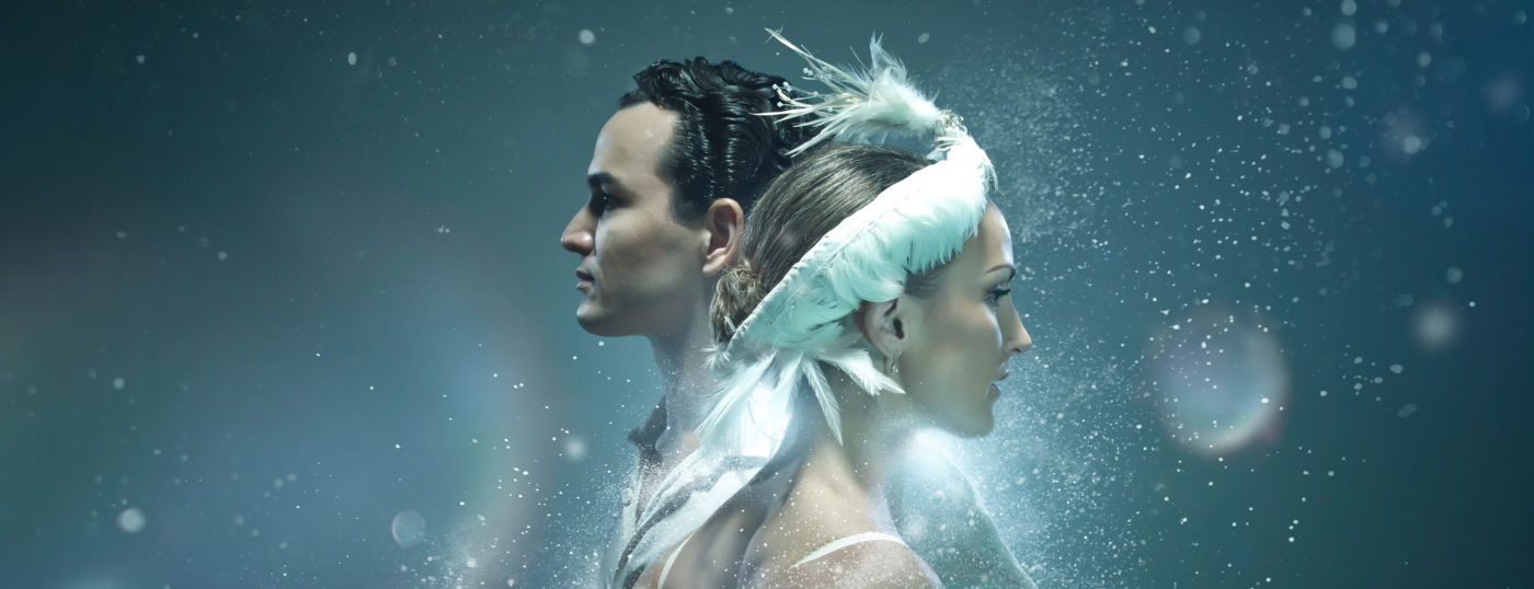 A promotional image for Swan Lake. Dancers Hannah Bateman and Javier Torres are shown from the shoulder upwards. Hannah looks to the right, and behind her Javier looks off to the left. She is wearing a feathered headdress, his dark wavy hair glints in the bright light flaring behind them as ice hangs in the air.