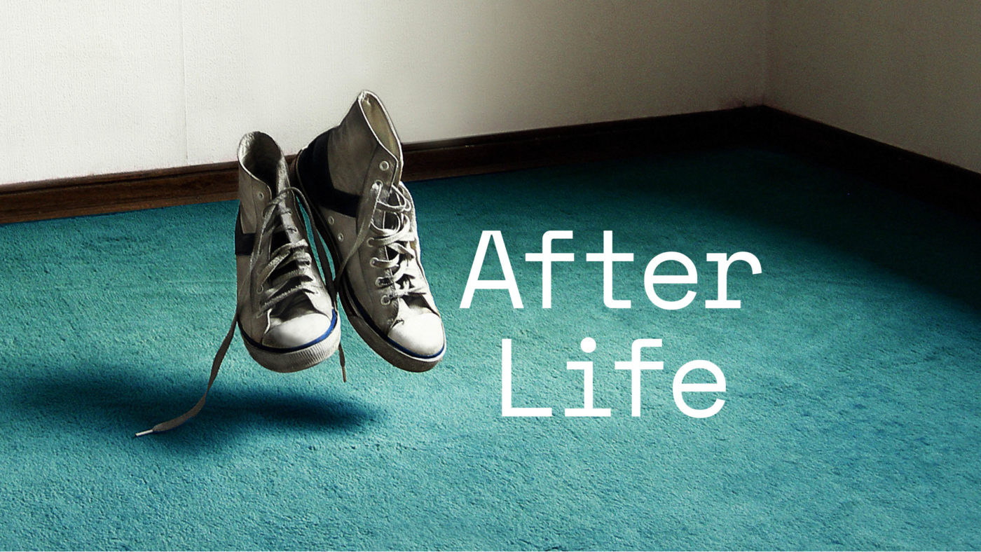 A pair of cream battered canvas shoes float a few centimetres above a worn teal carpet.