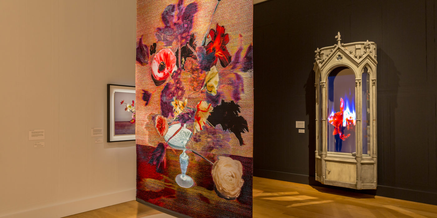 One of the rooms at the new Unearthed exhibition, at Dulwich Picture Gallery. In the foreground, a tapestry with flowers and a vase hangs from the ceiling. In the background, another art work