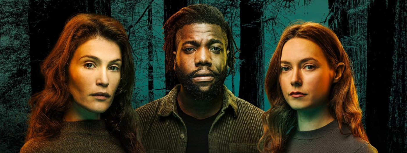 Three people seen from the shoulders up all stare out at us with serious faces. From left to right: Gemma Arterton, Fehinti Balogun and Lydia Wilson, each wearing dark green clothes that blend with their surroundings. Behind them the trunks and branches of very tall trees are silhouetted against a green sky.