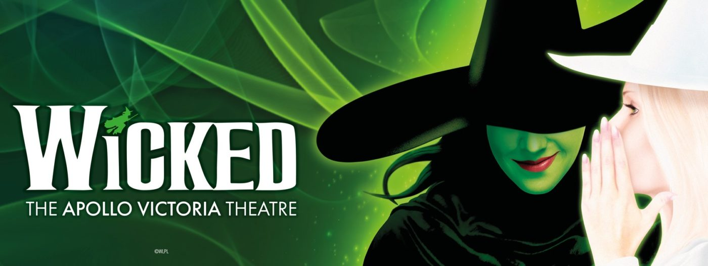 """Against a green background of swirling lights, in white text: Wicked (with a small green witch acting as the dot above the """"I"""") The Apollo Victoria Theatre. On the extreme right, head and shoulders in profile - the pale skinned and almost white haired good witch in white hat and robes has her hand raised covering her mouth as if whispering to the Wicked witch next to her and facing us. The wicked witch has jet black hair, robes and hat – whose rim covers her eyes – her green skin and bright red lips in a crooked smile."""