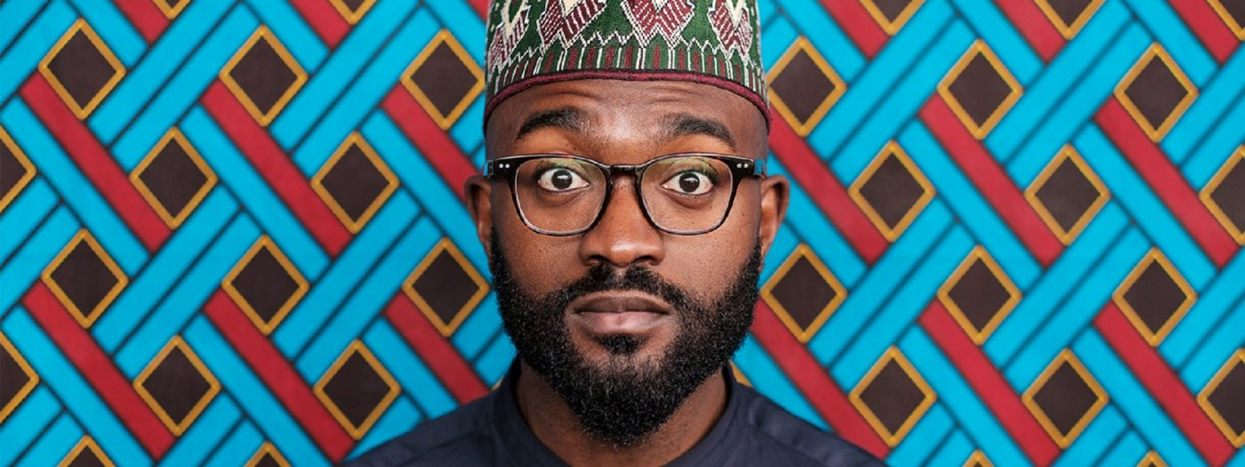 Inua Ellams stares at the spectator with wide eyes. He wears a black shirt, black glasses and a Nigerian Kufi hat. The background resembles a weaving pattern with thick strips of blue and red that interlink creating brown rhombuses.