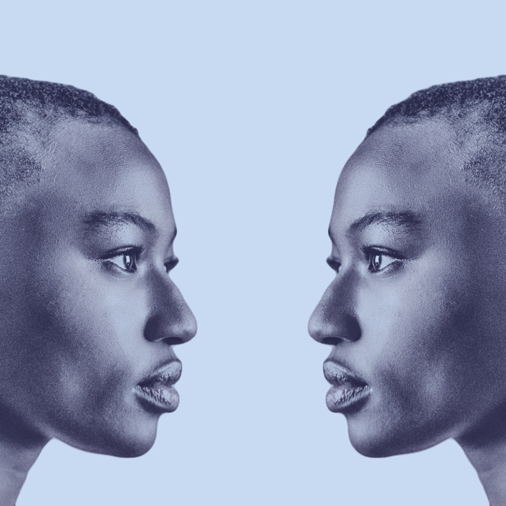 The profile of two twins, Racine and Anaia face each other, staring in to each other's eyes.