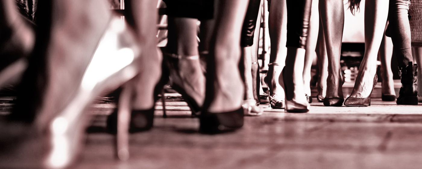 sepia toned image of several women's ankles and feet, all wearing high heels.