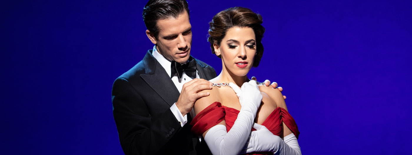 A Blue background shifting from almost black on the left to a mid-blue on the right. In the centre the actor Danny Mac playing Edward Lewis, is dressed in black bow tie and dinner jacket. He is stood behind Aimie Atkinson as Vivian Ward, he looks down with his hands on her bare shoulders, perhaps putting the large necklace currently over her shoulders on to her. She is wearing a low-cut red dress and white gloves to above the elbow. She looks down and backwards while one arm is held diagonally up cross her chest to the necklace and the other horizontally across her body.