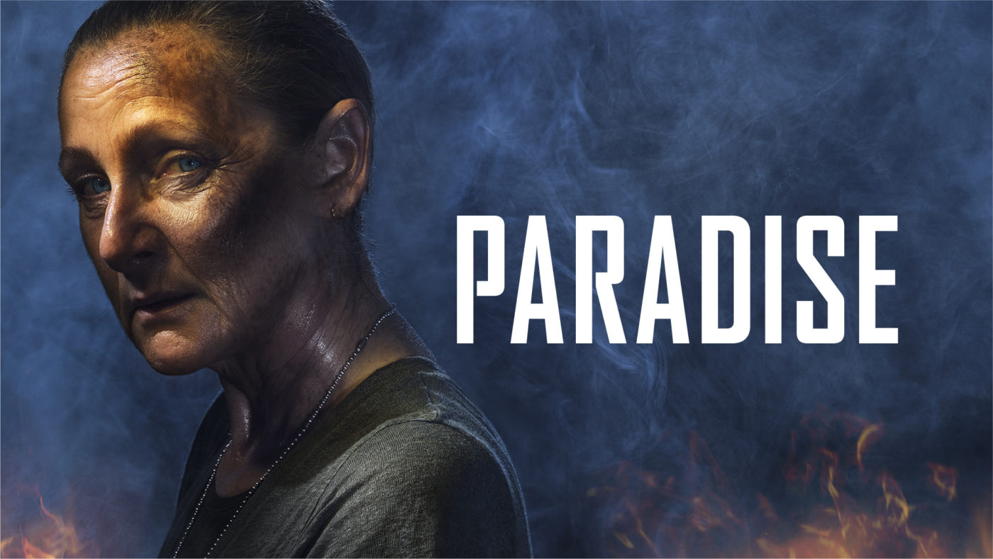 Philoctetes is seen from the shoulder upwards in a smoky blue background. Her brown hair is scraped back off her face with a dirty and sweaty complexion. She has blue eyes and seems lost in her stare. Text reads Paradise