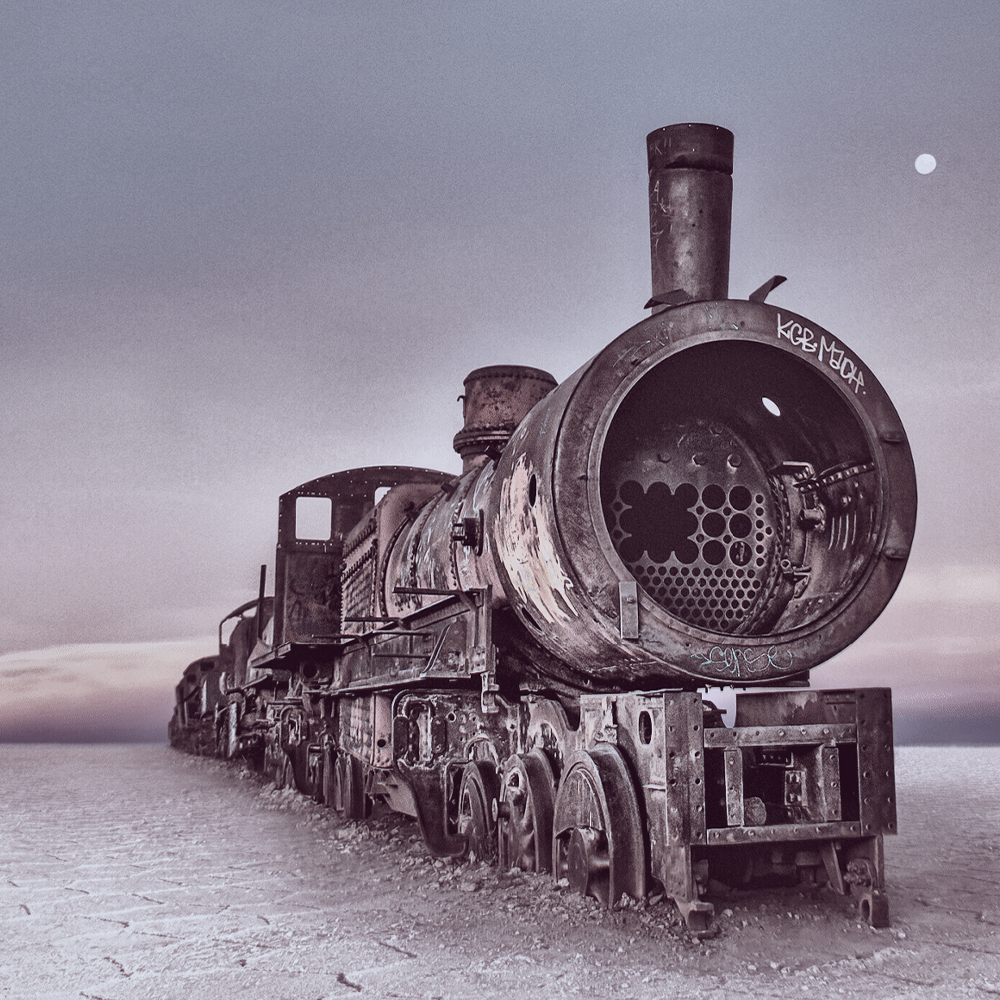 The shell of a train constructed of metal with graffiti on the front lays across a desert landscape.