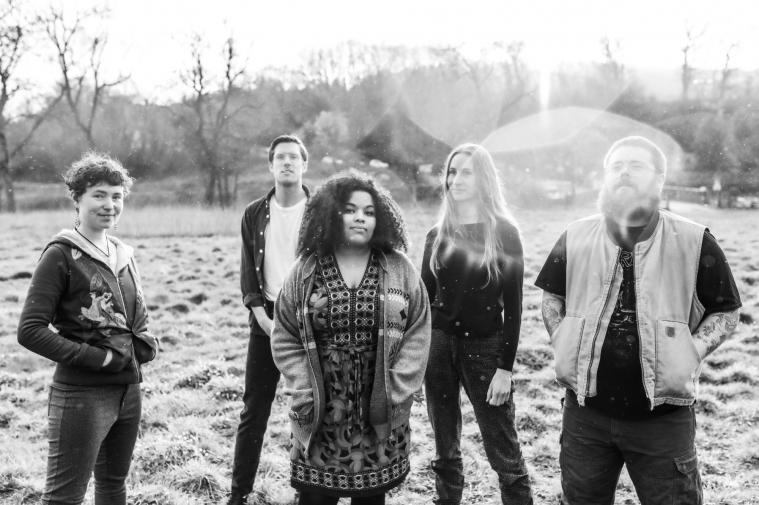 A black and white photograph with flares from the Sun. A group of young adults, three women and two men – are all stood together (but spread apart) in a field. They all wear casual clothes and look in our direction.
