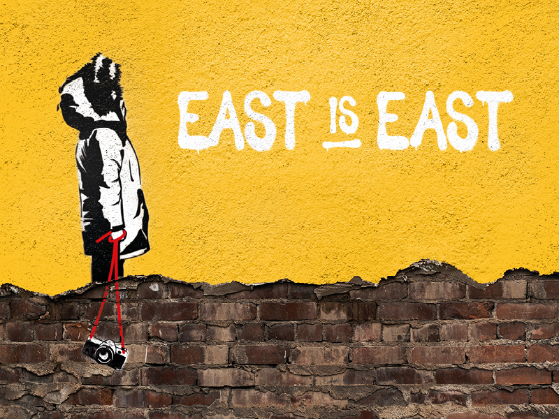 A brick wall partially painted yellow has a graffiti style image of a child in a large parka jacket holding a camera on a red strap. Beside him are the words East is East.