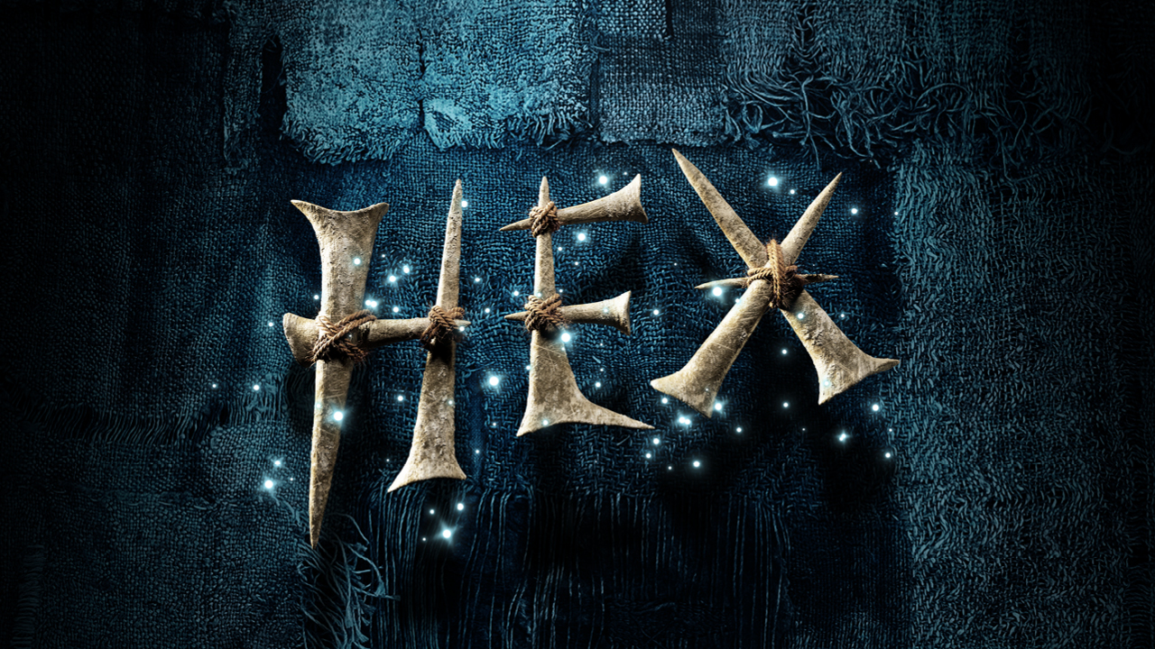 Rough metal stakes have been tied together to form the word HEX. Stars twinkle around the magic letters which appear on a dark frayed cloth.