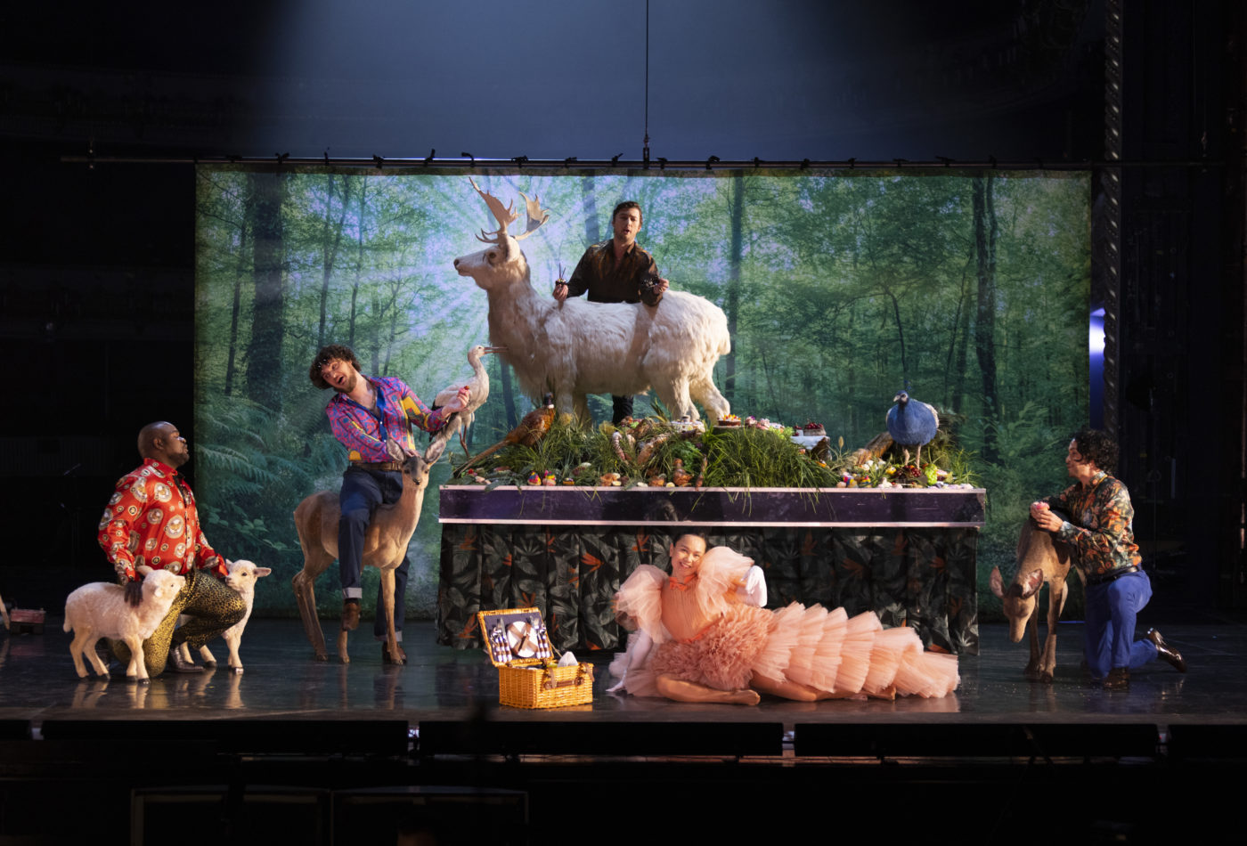 Artists Blaise Malaba, Egor Zhuravskii, Dominic Sedgwick, Jonadette Carpio and Filipe Manu in the JPYAP's Production of The Seven Deadly Sins. They wear bright, extravagant outfits and are sitting on and around life-sized fake lambs and deer, in front of an image of a forest. (c) ROH Photography by Ellie Kurttz