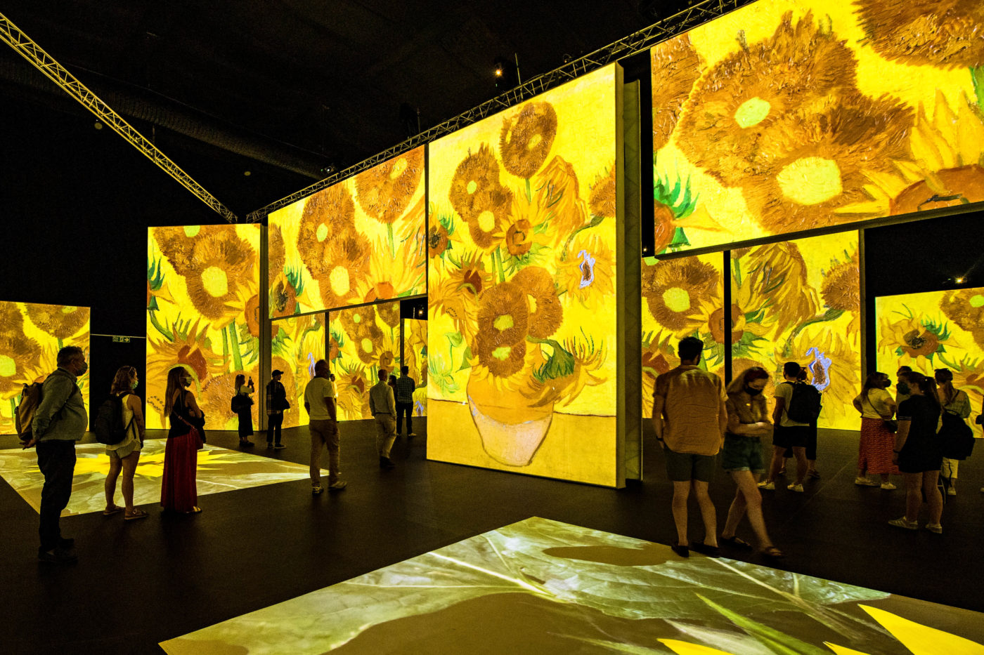 A big exhibition space divided by walls that work as screens, where Van Gogh's Sunflowers are projected. Audience members move around the space, getting different views of the artwork (from the picture as whole to detailed close-ups).