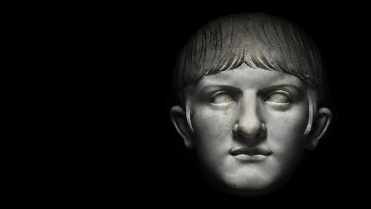 A marble bust of a young Nero stares out from a black background.