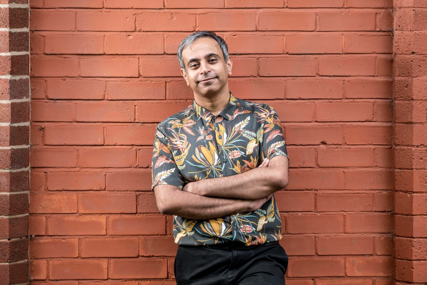 Shahid Iqbal Khan stands with arms crossed, leaning against a brick wall and wearing a floral print shirt. He is smiling gently.