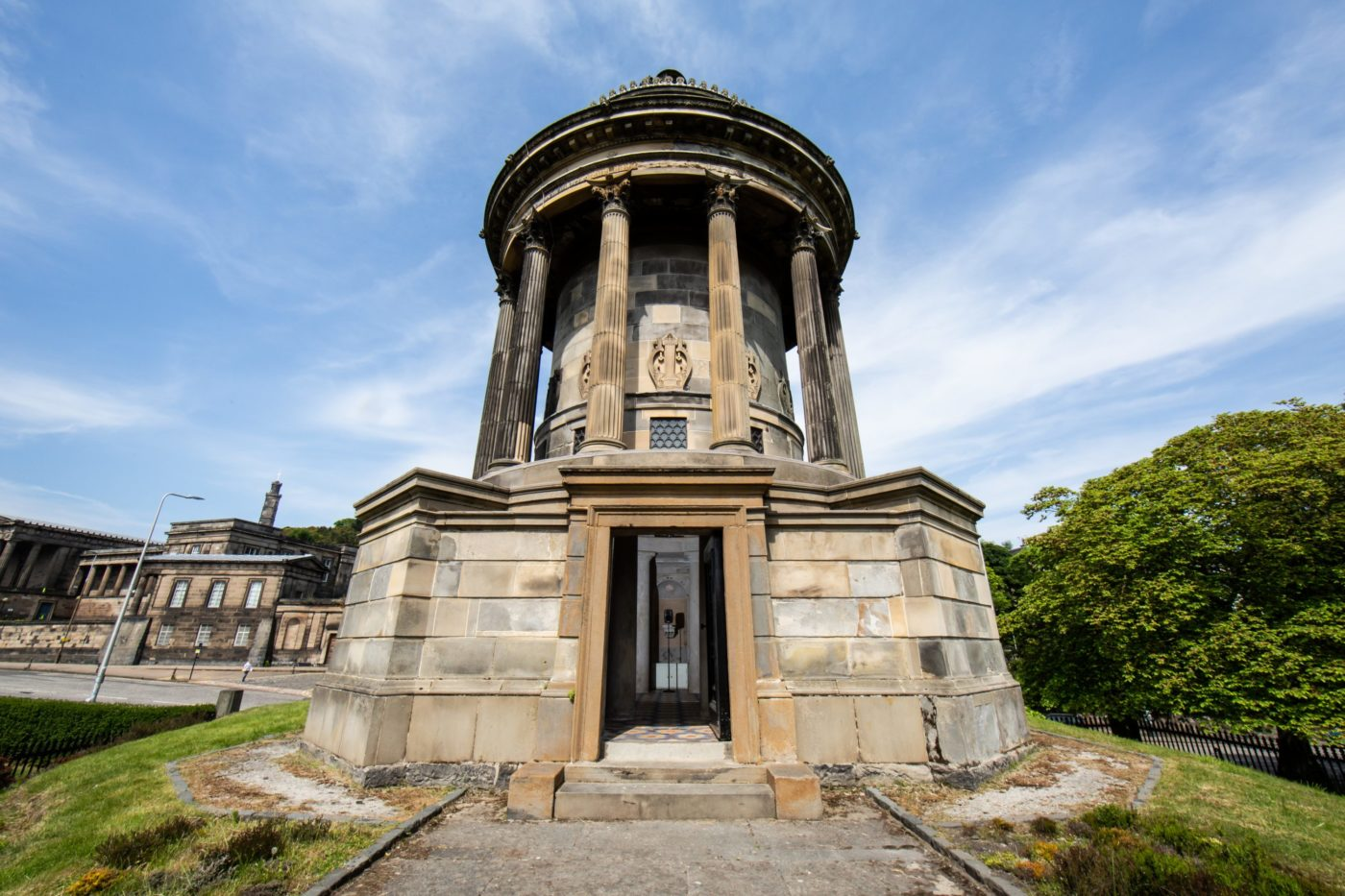 In the centre the Burns Monument dominates as the image has been taken from a low angle. The Monument is a neoclassical building, made of sandstone, with six columns supporting the roof of the building. A stone path is in the lower centre of the image, with grass verges on either side, showing the slight hill in which the Monument stands. In the doorway of the image is a tall free-standing speaker. On the right hand side is a green luscious tree, with a black wrought iron fence dividing the tree from the grass verge of the Burns Monument. In the background on the left is the Old Royal Highschool with Calton Hill's Nelson Monument visible in the centre above the Old Royal Highschool building. In front of the Old Royal Highschool is Regent Road, with a street light, and a green hedge dividing the road from the grass verge of the Monument.