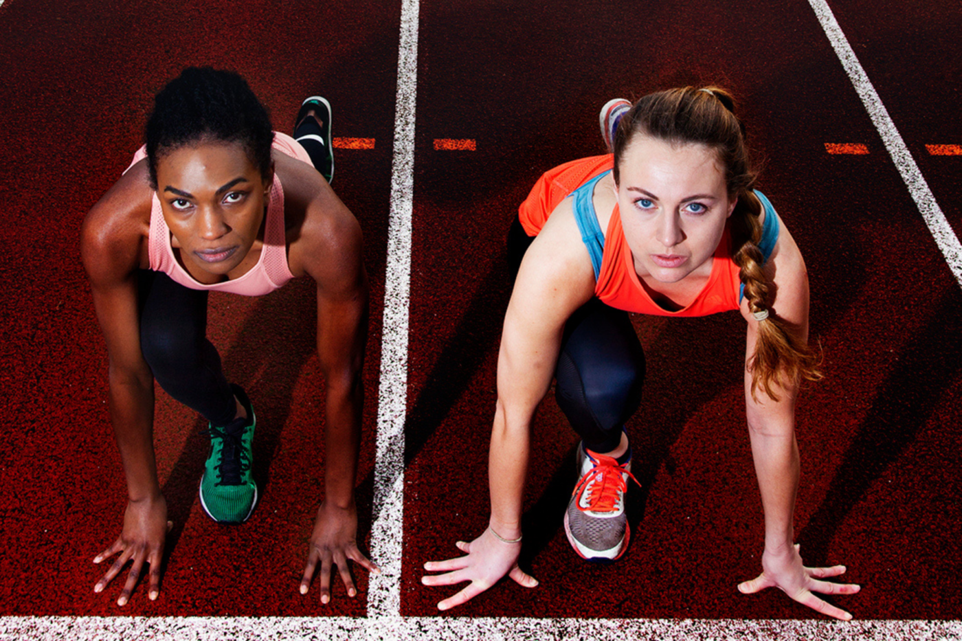 Two women in starting positions on a deep red running track, separated by white lane markings, both in running leggings, vest tops and trainers. To the left, a black woman with hair tied back. To the right, a white woman with plaited ponytail.