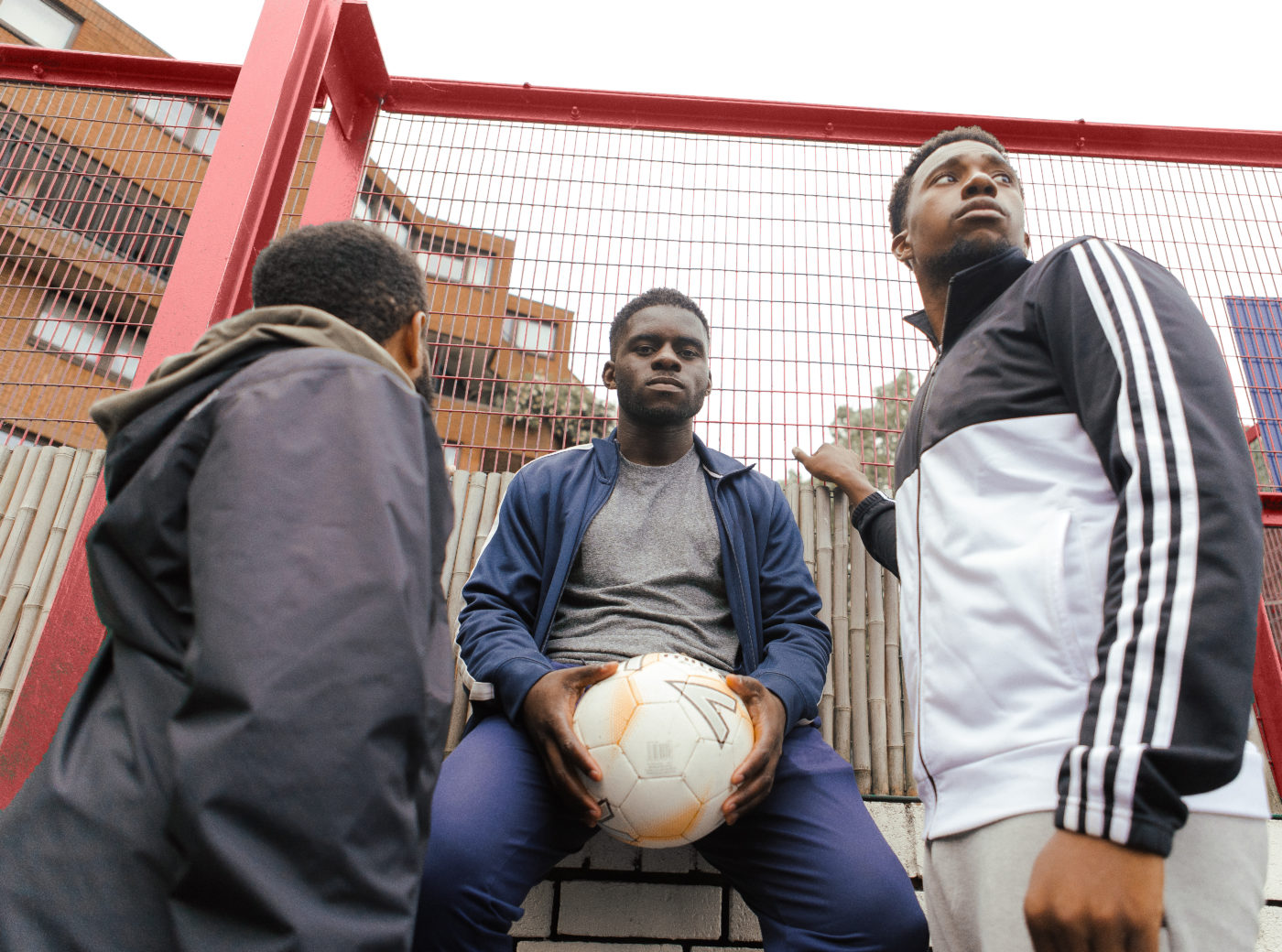 Three young black men. One sits on brick wall holding a football; one looks off into the distance; one, with his back to us, is looking through the red metal fence to flats and the grey sky beyond.