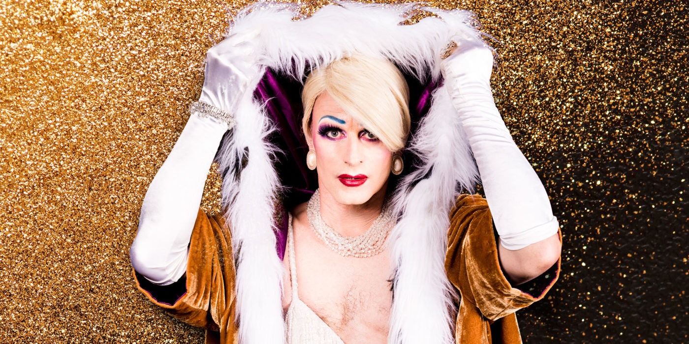 A glamorous white person with elegant blue eyebrows, red lips and pearl earnings lifts a fur-trimmed purple hood above their head. They are wearing white opera gloves and are in front of a gold glitter background.