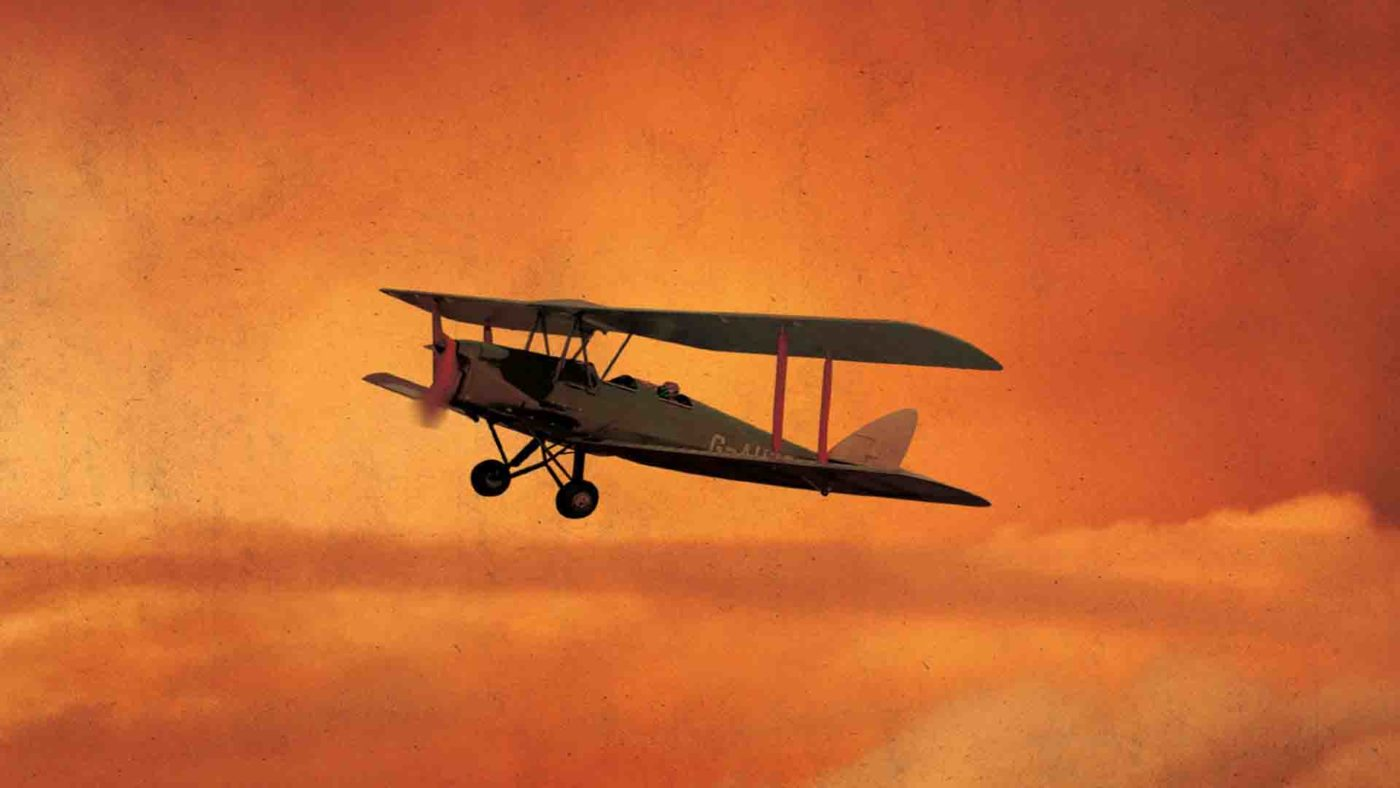 Against an orange sky, a Gipsy Moth bi-plane heads above the clouds, its propeller whirring. One single pilot is visible in the open back seat.