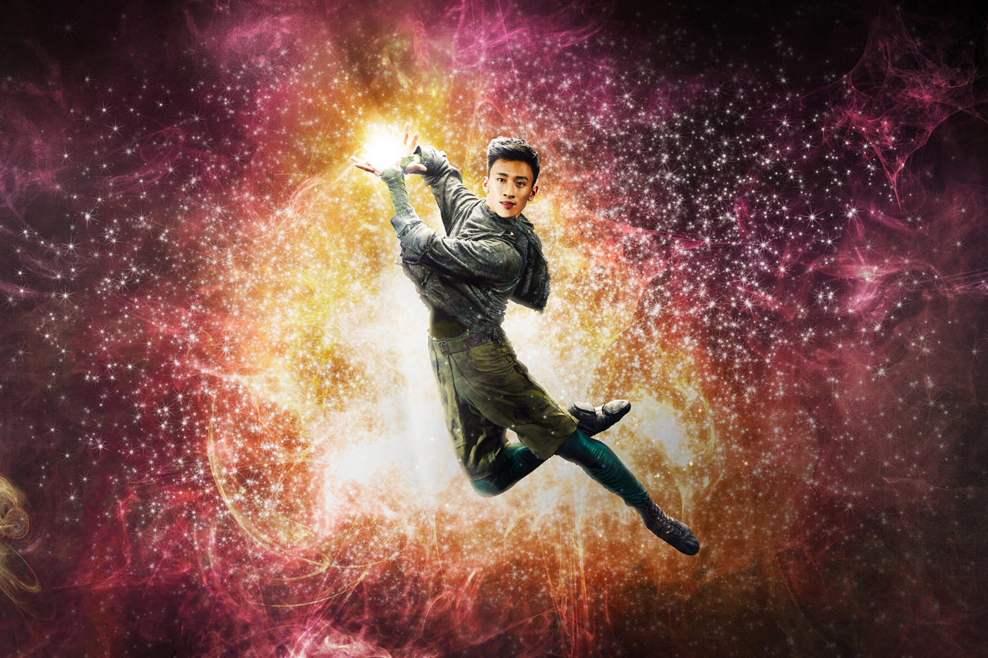 Dancer Matthew Koon as Merin, leaps up, his hands cradling a bright flash of light. Behind him is a magical swirl of stars. Across the front of the picture is the word, Merlin.
