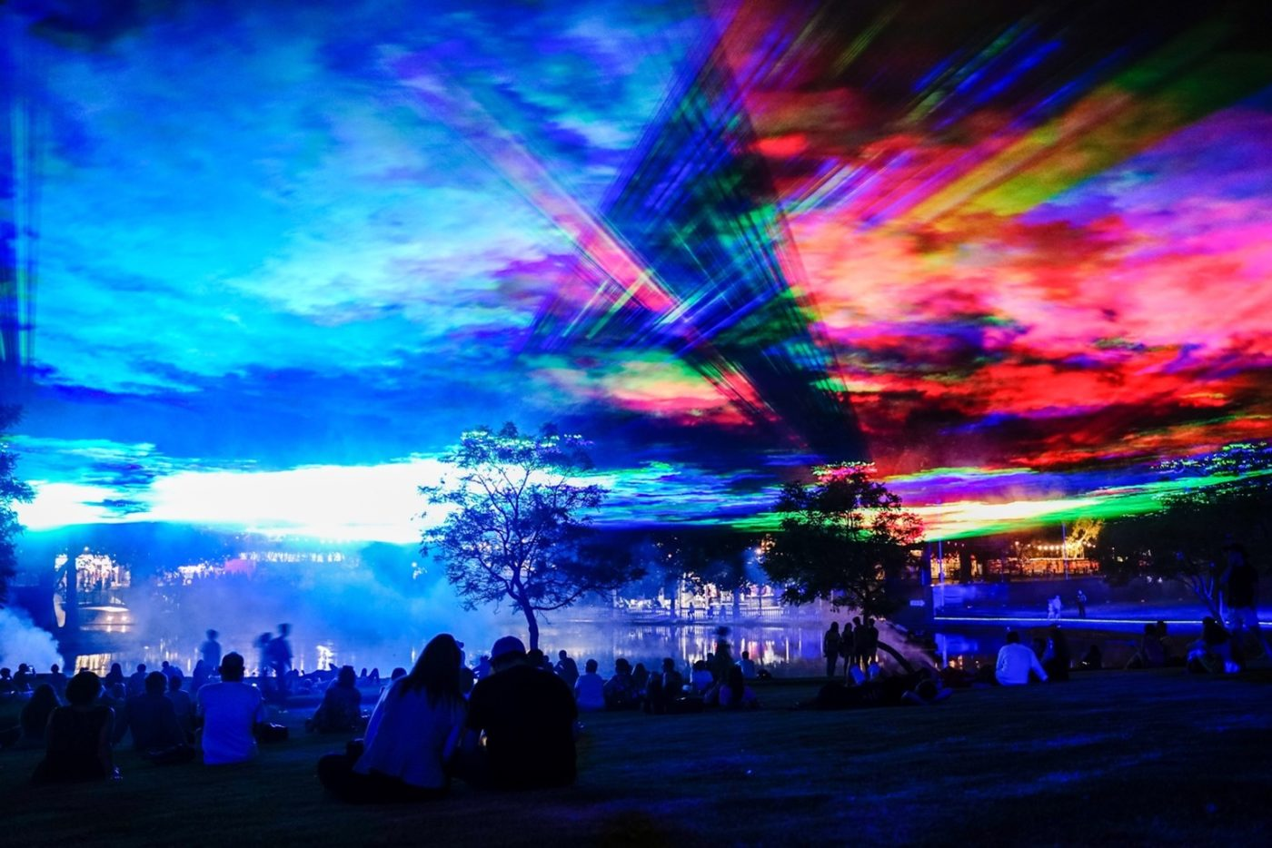 From Greenwich + Docklands International Festival, the aurora borealis is recreated with multi-coloured lights over a night sky in a city park. Couples and groups watch from below.