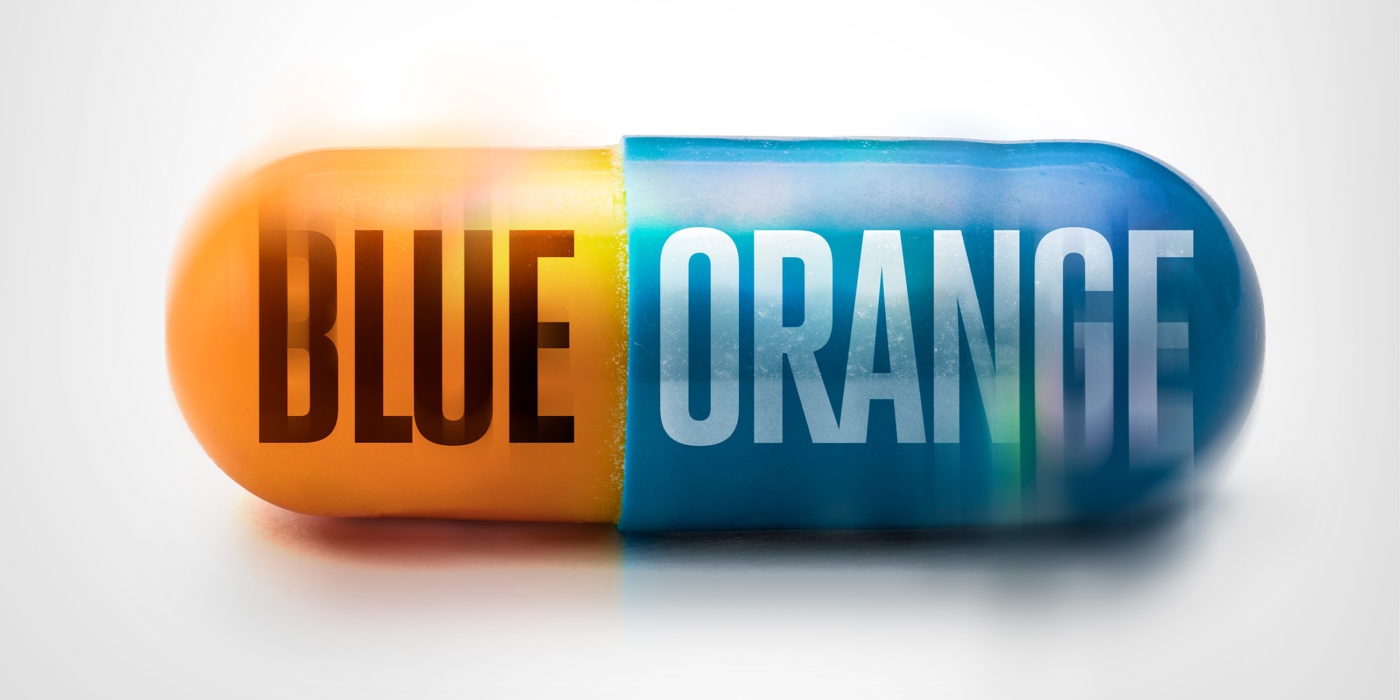 A blue and orange pill appears blurred, as if it's rolling along a surface. The two-coloured pill is labelled blue on the orange section, and orange on the part that's blue.