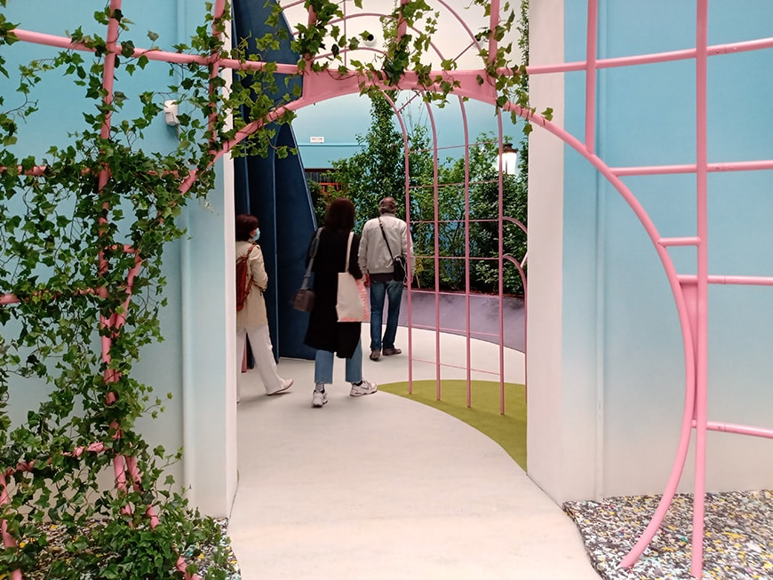 Three visitors make their way through The Garden of Privatised Delights at the UK Pavilion at Venice Biennale. A metal frame, painted pink and covered with ivy, creates a circular doorway for them to enter the exhibition.