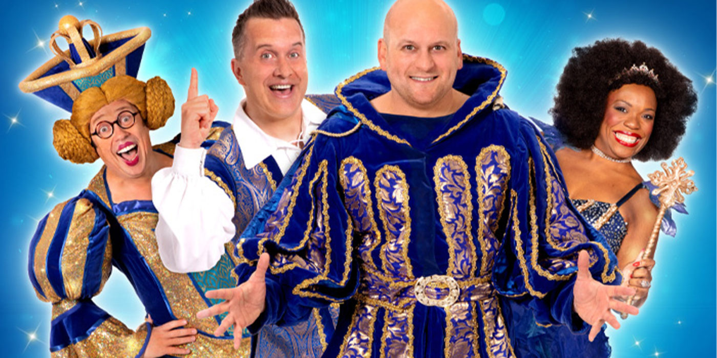 Four actors smile enthusiastically. Ricky Champ, in a regal blue tunic, has his hands outstretched; Deborah Tracey is holding a magic wand; Phil Gallagher points his finger in the air; and Bob Golding, with a corn-yellow Princess Leia-style wig and a gold and blue dress, is giving a look of delight.