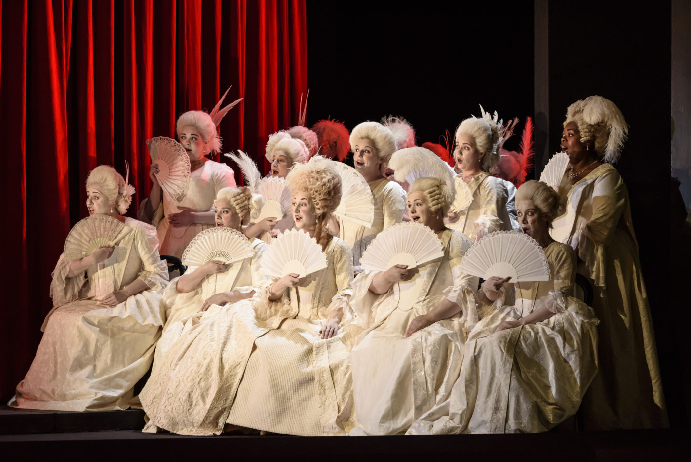 A chorus of ten women, each dressed in white with a open fan held at her chin. They wear powdered wigs and heavy chalky makeup, and sing as they watch with delight at what is happening on stage. Photo credit: Bill Cooper.