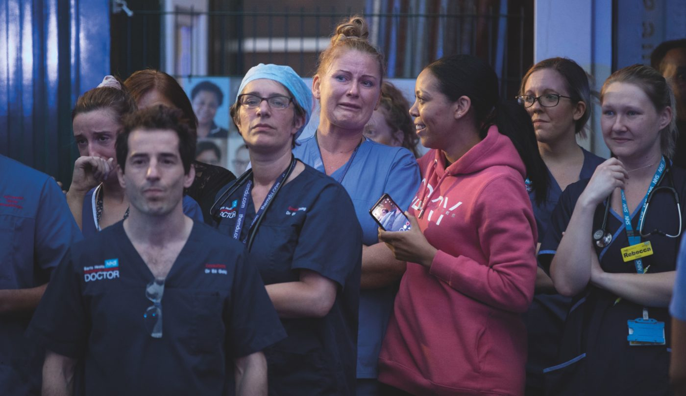 A group of health workers gather outside of the emergency department at Newham University Hospital for the first ever clap for the NHS in the first wave of the Covid-19 pandemic. Some people are crying, some are smiling. Emma Young (emergency physician) stares down the photographer's lense.