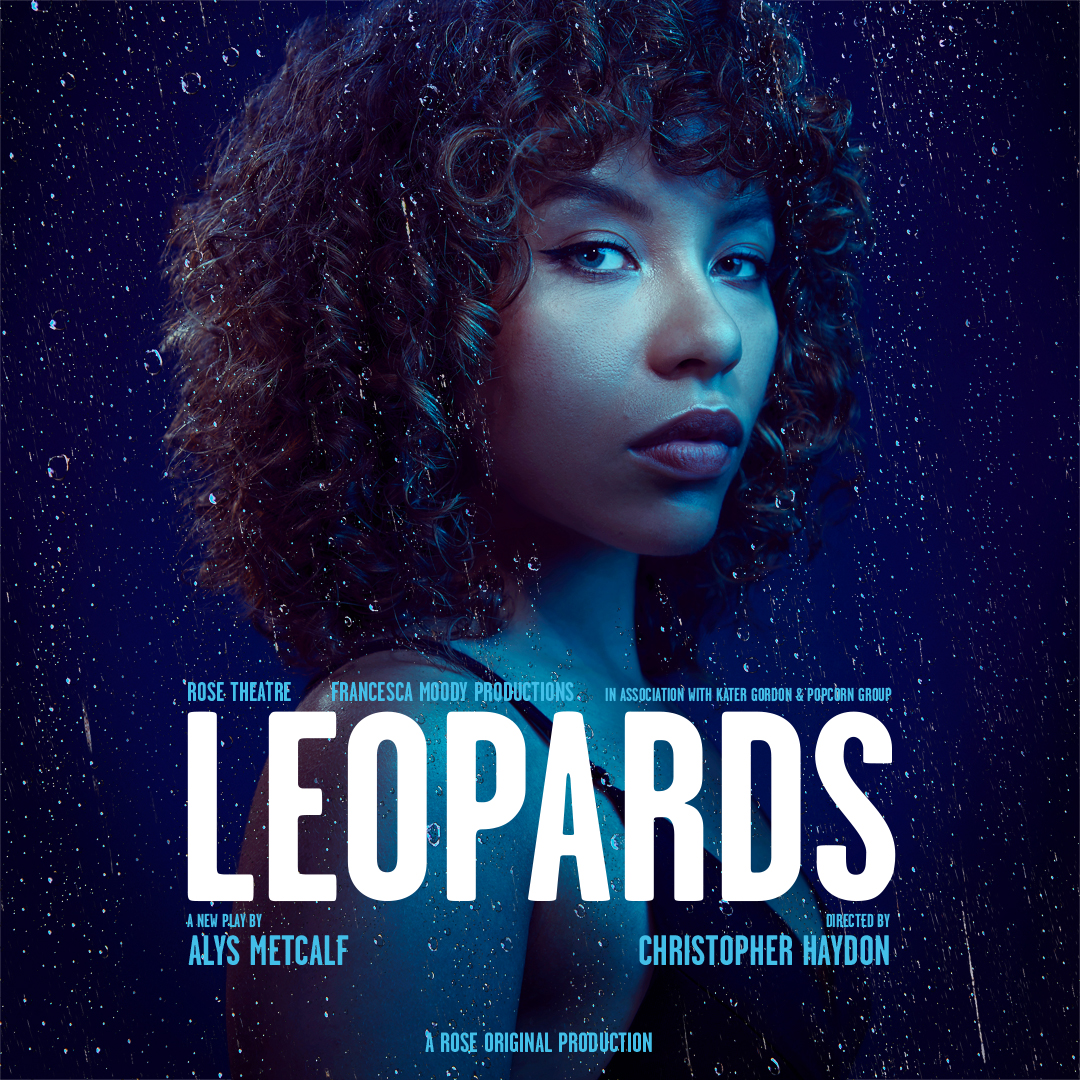 Actor Saffron Coomber looks straight ahead with a serious expression. The image is tinted blue and set against a dark blue background with raindrops. Text reads 'Rose Theatre, Francesca Moody Productions, in association with Kater Gordon & Popcorn Group. LEOPARDS. A new play by Alys Metcalf, directed by Christopher Haydon. A Rose Original Production.