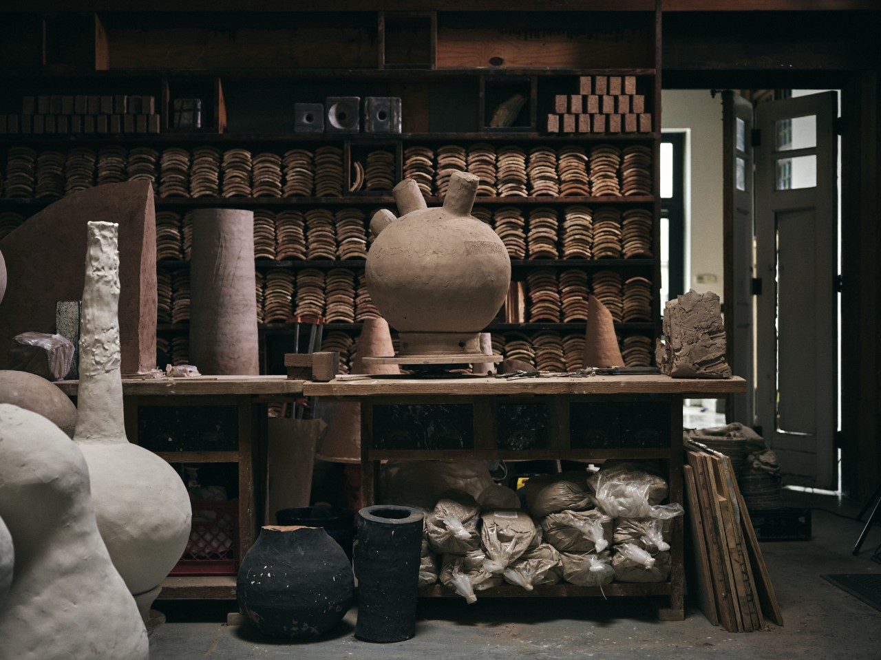 A photograph of an artists' workshop. In the centre is a large workbench with bags of clay piled beneath it. On top of the workbench is a large tan-coloured spherical clay sculpture with three tubular shapes protruding from its top. In the foreground are more vessle-like clay sculptures, ranging from burnt black to pale grey in colour. In the background, the walls of the workshop are covered in dark wooden shelves which are filled with terra cotta roof tiles. To the far right of the image, a white folding door is left ajar.