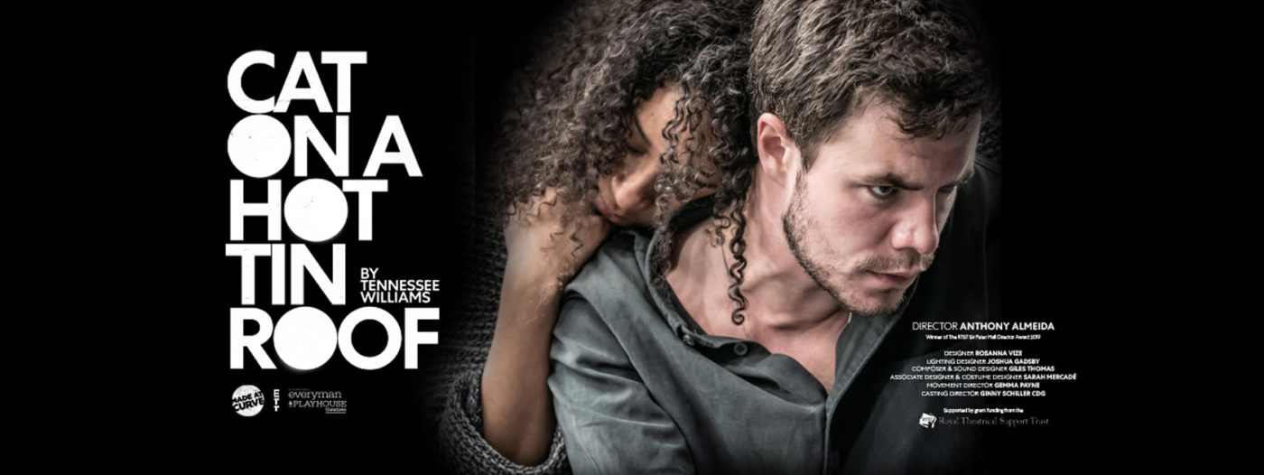 Actor Oliver Johnstone is staring forward intensely, seething with anger. Actor Siena Kelly, is embracing him from behind, with her head on his shoulder and her hair falling down onto his neck.