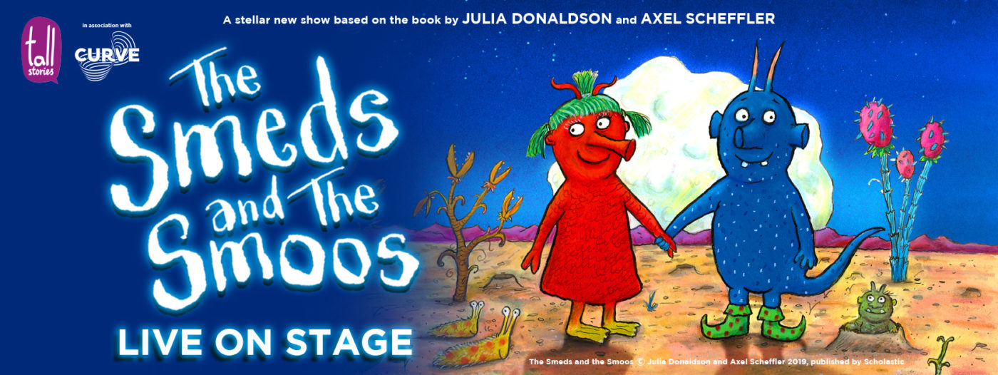 A red alien with green pigtails and yellow feet holds hands with a blue alien with orange horns and green shoes in an illustrated image from The Smeds and The Smoos. They stand on the surface of a yellow planet beneath a blue sky, surrounded by unusual plants and two yellow slug creatures with orange polka dots. A small green alien is popping out a crater behind them, and a pink mountain landscape can be seen in the distance. White, glowing text reads 'The Smeds and the Smoos - Live on Stage.' Smaller white text reads 'A stellar new show based on the book by Julia Donaldson and Axel Scheffler.'