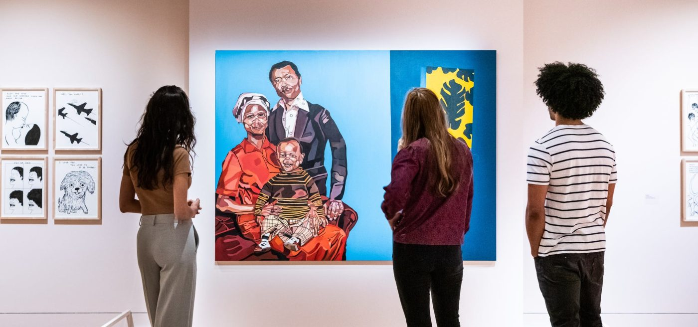 Three people look at a painting at the Wellcome exhibition 'On Happiness'. The picture is a stylised family portrait of a mother and father with a smiling baby.
