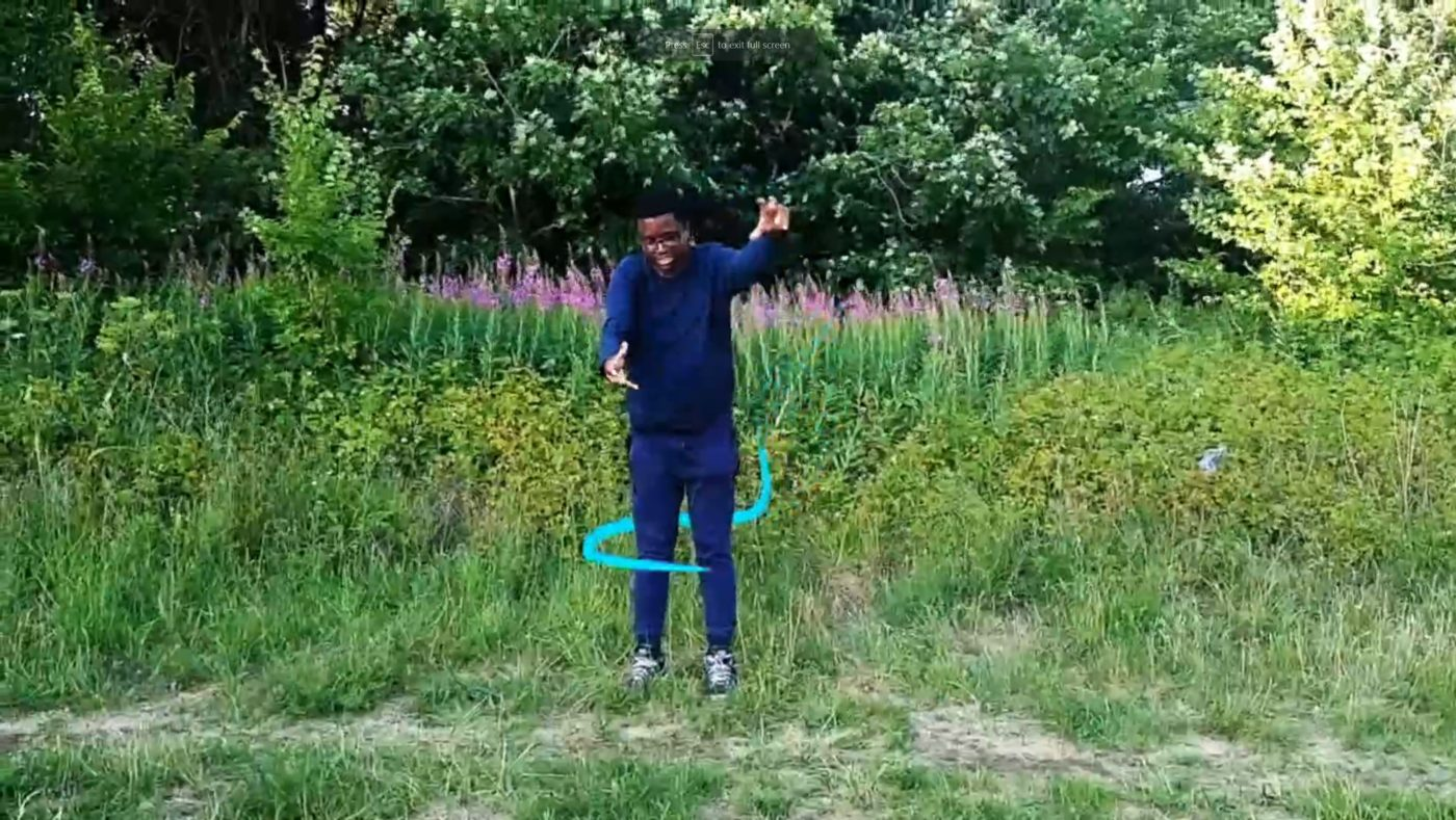 From the audio described film, Knowing Togetherness. Before a thick tapestry of green, a man is dancing, his arms outstretched. He smiles joyfully as an animated blue line circles around his body.