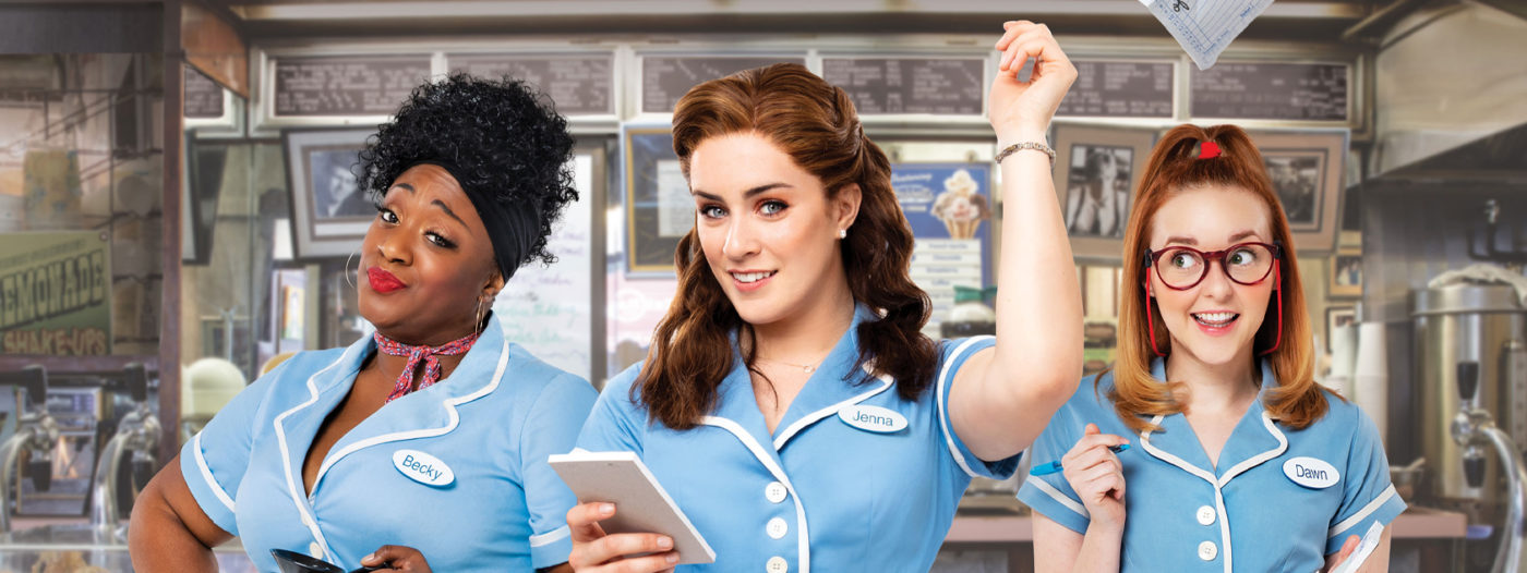 Three waitresses in diner uniforms stand together. One holds a coffee pot and gives a knowing look, another is poised to take down an order on her pad. In the centre, the third waitress has ripped a page from her note pad and flings it into the air.