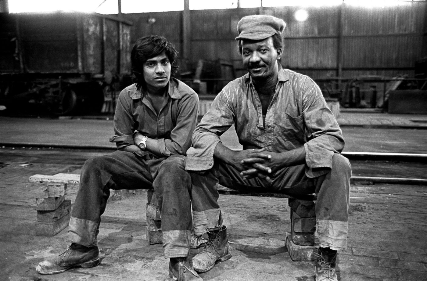 Two men sit on a bench in a train depot, wearing workman's clothes. The younger of the two, of South Asian origin, sits with his arms folded. The other, a black man, wears a cap, rests his elbows on his knees and smiles.