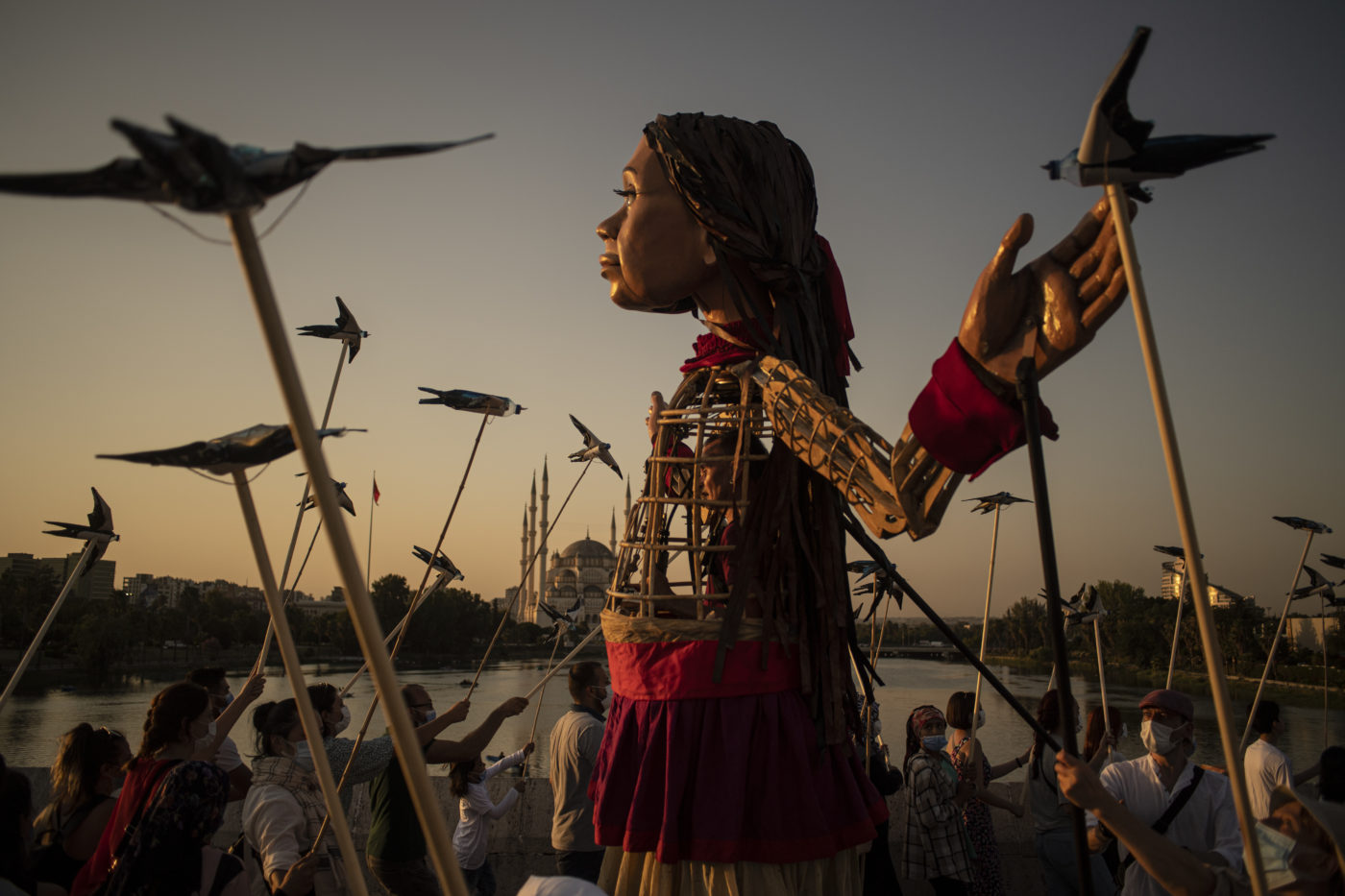 The puppet of Amal stands facing into the setting sun. She is surrounded by puppeteers holding swallow puppets on long sticks. Amal's arms are outstreched.