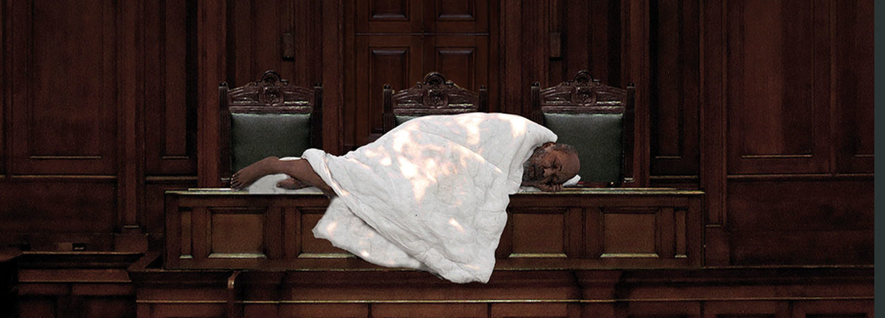 From the Austerity Museum, a picture of a very thin, older man wrapped in a duvet on a judge's table in a courtroom. His bare feet poke out from his meager cover as he sleeps in front of three empty leather-bound chairs.