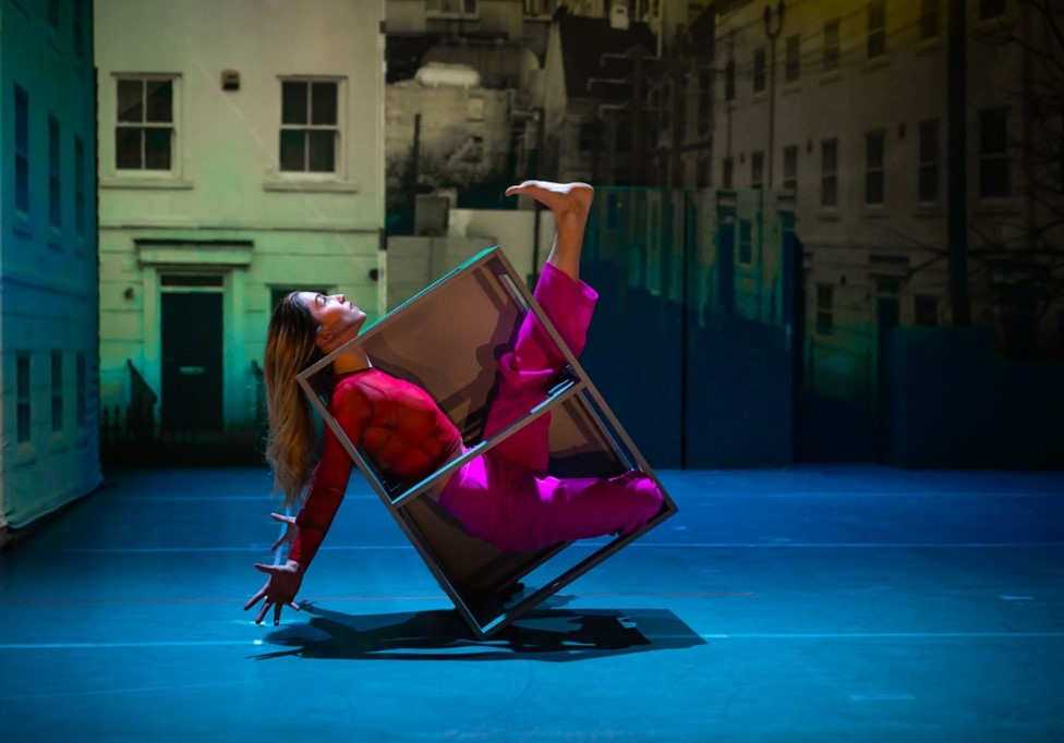 A female dancer in a pink top and trousers, is on stage, her body enclosed inside a metal box. She is balancing on one corner of the box, her arms outstretched behind her and one foot extended and flexed. Her head is outside the box and looking upwards. Behind her is a projection of a residential street.