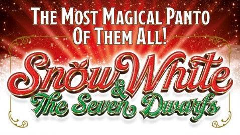 On a red background with snowflakes illuminated by rays of light, are the words Snow White & The Seven Dwarfs. The o in Snow White is the shape of a red apple. Above it reads, The Most Magical Panto of Them All!